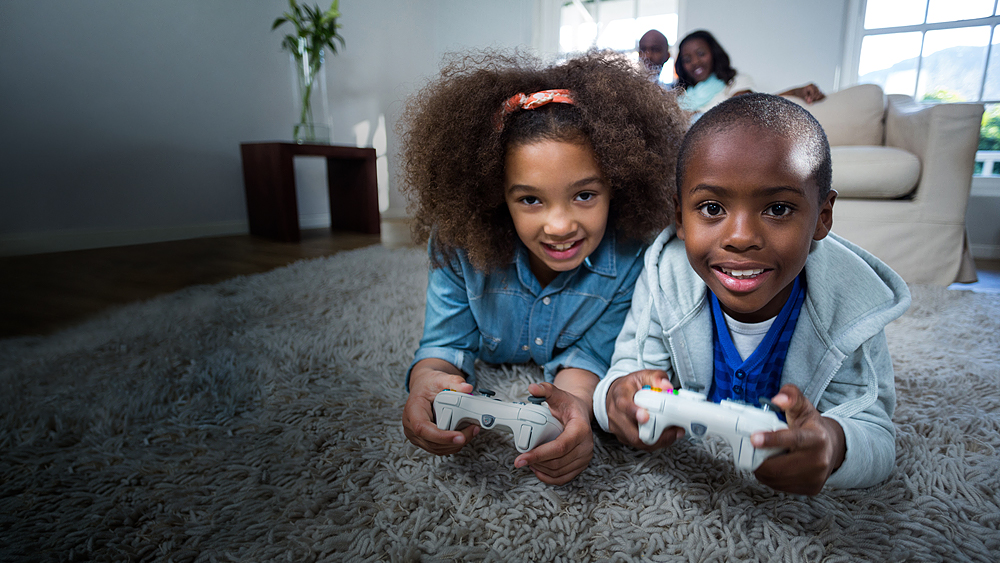 Wellspect Navina Smiling siblings at home lying on carpet, playing video game