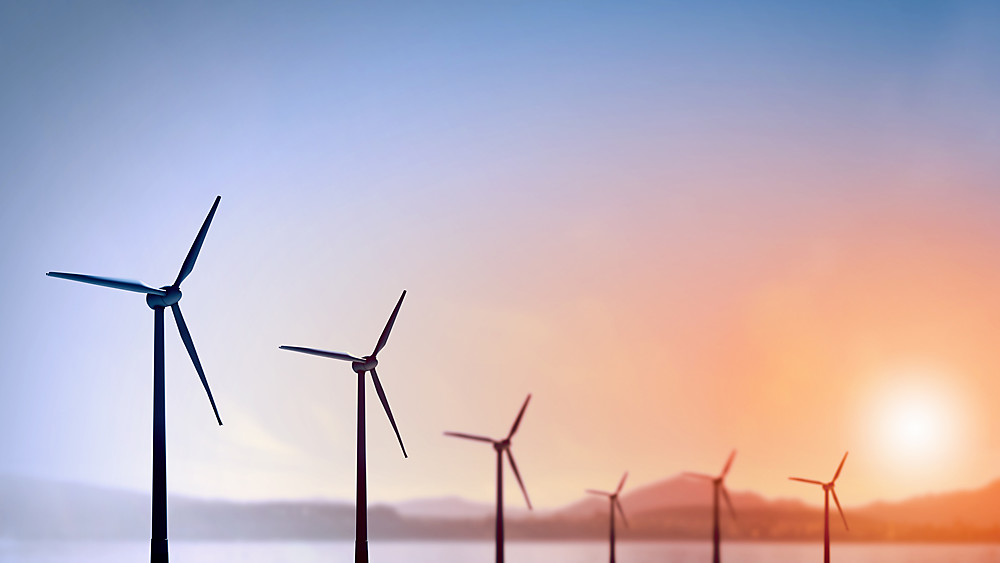 Wellspect About Row of wind turbines with sunset in background
